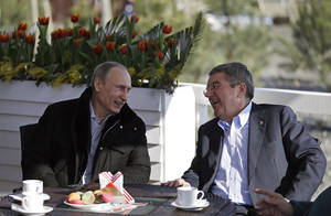 Photo - Russian President Vladimir Putin, left, and International Olympic Committee President Thomas Bach sit at a cafe along the promenade on the Black Sea near the Olympic Park at the 2014 Winter Olympics, Saturday, Feb. 15, 2014, in Sochi, Russia. (AP Photo/David Goldman)