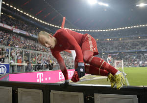 photo - Bayern's Arjen Robben of Netherlands jumps over the bench to gift his shirt after the German first division Bundesliga soccer match between FC Bayern Munich and FC Schalke 04 in Munich, Germany, Saturday, Feb. 9, 2013. Bayern defeated Schalke with 4-0. (AP Photo/Martin Meissner)