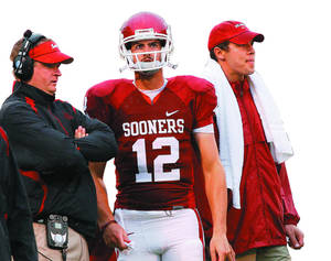 Photo - OU QB coach Josh Heupel, left, Landry Jones and Sam Bradford look on from the sideline during the first half against Idaho State.  Jones waited a first half before he was handed the scepter of Oklahoma football. Asked to command the huddle and lead the Sooners to victory and become a state icon. Photo by Chris Landsberger, The Oklahoman