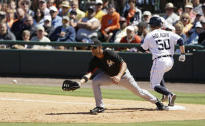 Photo - Detroit Tigers' Bryan Holaday safely beats the throw to Miami Marlins first baseman Garrett Jones to allow Torii Hunter to score from third during the fourth inning of a spring exhibition baseball game in Lakeland, Fla., Thursday, March 13, 2014. (AP Photo/Carlos Osorio)