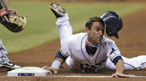 Photo - Tampa Bay Rays' Sam Fuld loses his helmet as he dives back to first base on a third-inning pickoff attempt during a baseball game against the Seattle Mariners on Thursday, Aug. 15, 2013, in St. Petersburg, Fla. (AP Photo/Chris O'Meara)