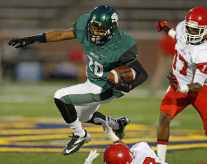 Photo - Edmond Santa Fe's Cameron Westbrook  leaps over Lawton's Kevin Bell as Kalin Sadler chases during their high school football game at Wantland Stadium in Edmond, Okla., Thursday, October 11, 2012. Photo by Bryan Terry, The Oklahoman