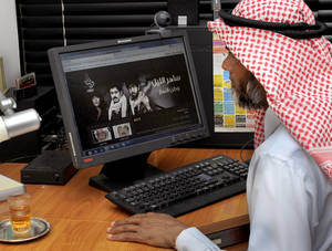 """Photo -   In this Monday, Aug. 13, 2012 photo, a Kuwaiti man watches Alrai TV drama series """"Saher al lail"""" online in his house in Salwa, Kuwait. Each night for the past three weeks, families in Kuwait have been transfixed by a drama in which they already know the ending: Iraq forces will be driven out and the shattered Gulf nation will rebuild. But a 30-part television serial on Iraq's 1990 invasion has become more than just a retelling of the occupation and the brief but intense Gulf War. The series is being seen by many as a reminder of past national unity at a time when Kuwait is caught in a near endless cycle of tribal bickering and political showdowns between the Western-backed ruling family and conservative Islamists, who want to impose measures such as banning public concerts and blocking women athletes from major sporting events. Tensions over the Gulf Arab showdowns with Shiite power Iran also have brought pressures on Kuwait's minority Shiites.(AP Photo/Gustavo Ferrari)"""