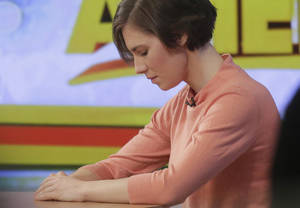 "Photo - Amanda Knox bows her head during a television interview, Friday, Jan. 31, 2014 in New York. Knox said she will fight the reinstated guilty verdict against her and an ex-boyfriend in the 2007 slaying of a British roommate in Italy and vowed to ""never go willingly"" to face her fate in that country's judicial system . ""I'm going to fight this to the very end,"" she said in an interview with Robin Roberts on ABC's ""Good Morning America."" (AP Photo/Mark Lennihan)"