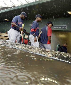 Photo - Boston Red Sox designated hitter David Ortiz, left, and teammates exit the dugout after rain canceled the spring exhibition baseball game against the Baltimore Orioles in the second inning in Sarasota, Fla., Monday, March 24, 2014. (AP Photo/Carlos Osorio)