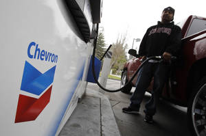 Photo - FILE - In this Jan. 28, 2011 file photo, a customer pumps gas at a Chevron gas station in Mountain View, Calif. Chevron Corp. reports quarterly earnings on Friday, May 2, 2014. (AP Photo/Paul Sakuma, File)