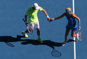 Photo - Kristina Mladenovic of France and Daniel Nestor of Canada celebrate a point won against Sania Mirza of India Horia Tecau of Romania during the mixed doubles final at the Australian Open tennis championship in Melbourne, Australia, Sunday, Jan. 26, 2014.(AP Photo/Eugene Hoshiko)