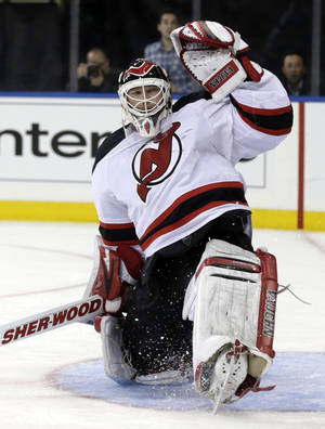 Photo - New Jersey Devils goalie Martin Brodeur makes a save during the second period of an NHL hockey game against the New York Rangers, Sunday, April 21, 2013, in New York. The Rangers defeated the Devils 4-1. (AP Photo/Seth Wenig)