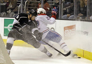 Photo - Montreal Canadiens right winger Dale Weise (22) and Los Angeles Kings defenseman Jake Muzzin (6) battle in the first period of an NHL hockey game in Los Angeles Monday, March 3, 2014. (AP Photo/Reed Saxon)