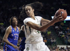 photo -   Baylor 's Brittney Griner (42) moves the ball against Kansas' Aishah Sutherland, rear, as Carolyn Davis (21) looks on in the second half of an NCAA women's college basketball game Saturday, Jan. 28, 2012, in Waco, Texas. Griner had seven rebounds, five blocks and 28-points in the 74-46 Baylor win. (AP Photo/Tony Gutierrez)