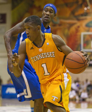 Photo - Tennessee guard Josh Richardson (1) drives past Memphis guard Will Barton in the first half of an NCAA college basketball game Tuesday, Nov. 22, 2011, in Lahaina, Hawaii. (AP Photo/Eugene Tanner)