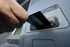 Photo -      A person demonstrates using a credit card at an ATM. AP Photo  <strong>Gene J. Puskar -   </strong>