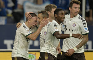 Photo - Bayern's Franck Ribery of France, left, is celebrated by teammates after scoring during the German soccer Bundesliga match between FC Schalke 04 and Bayern Munich at the arena in Gelsenkirchen, Germany, Saturday, Sept. 21, 2013.  (AP Photo/Martin Meissner)