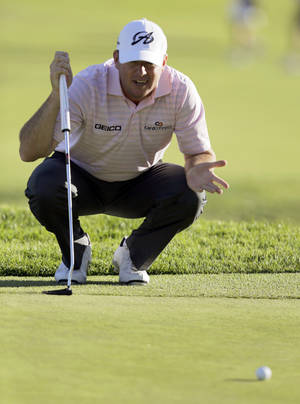 Photo - Robert Garrigus eyes what became his birdie putt on the ninth green in the second round of the Northern Trust Open golf tournament at Riviera Country Club in the Pacific Palisades area of Los Angeles, Friday, Feb. 14, 2014.  (AP Photo/Reed Saxon)