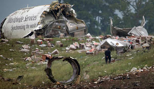 Photo - An investigator looks through debris of a UPS A300 cargo plane after it crashed on approach at Birmingham-Shuttlesworth International Airport, Wednesday, Aug. 14, 2013 in Birmingham, Ala. The two pilots aboard were killed. (AP Photo/Hal Yeager)
