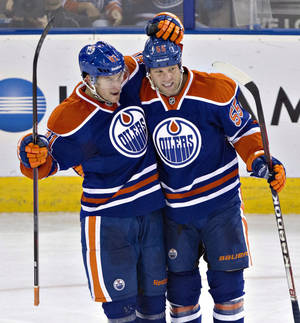 Photo - Edmonton Oilers' Taylor Fedun (81) and Ben Eager (55) celebrate a goal against the New York Rangers during the second period of an NHL hockey preseason game, Tuesday, Sept. 24, 2013, in Edmonton, Alberta. (AP Photo/The Canadian Press, Jason Franson) ORG XMIT: EDM109