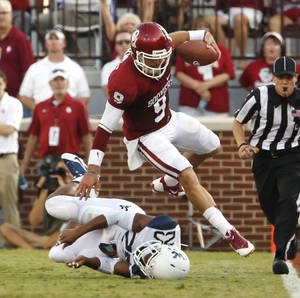 Photo - Oklahoma's Trevor Knight (9) is knocked out of bounds during a college football game between the University of Oklahoma Sooners (OU) and the West Virginia University Mountaineers at Gaylord Family-Oklahoma Memorial Stadium in Norman, Okla., on Saturday, Sept. 7, 2013. Photo by Steve Sisney, The Oklahoman