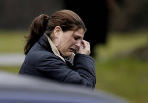 Photo - A mourner leaves the funeral service of Sandy Hook Elementary School shooting victim, Jack Pinto, 6, Monday, Dec. 17, 2012, in Newtown, Conn. Pinto was killed when a gunman walked into Sandy Hook Elementary School in Newtown Friday and opened fire, killing 26 people, including 20 children.(AP Photo/David Goldman)