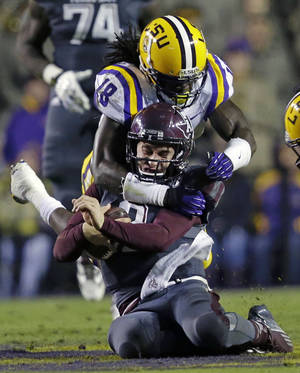 Photo - Texas A&M quarterback Johnny Manziel is tackled by LSU linebacker Lamin Barrow (18) in the second half of an NCAA college football game in Baton Rouge, La., Saturday, Nov. 23, 2013. LSU won 34-10. (AP Photo/Gerald Herbert)