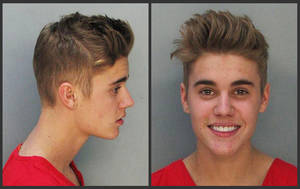 Photo - These police booking mugs made available by the Miami Dade County Corrections Department show pop star Justin Bieber, Thursday, Jan. 23, 2014. Bieber and singer Khalil were arrested early Thursday for allegedly drag-racing on a Miami Beach Street. Police say Bieber has been charged with resisting arrest without violence in addition to drag racing and DUI. Police also say the singer told authorities he had consumed alcohol, smoked marijuana and taken prescription drugs. (AP Photo/Miami Dade County Jail)