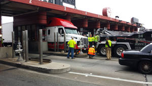 Photo - This photo provided by the Golden Gate Bridge, Highway and Transportation District shows a tractor-trailer that got stuck while trying to pass through the Golden Gate Bridge toll plaza Monday, July 1, 2013, in San Francisco. A a tow truck freed the truck after about 2 ½ hours. (AP Photo/Golden Gate Bridge, Highway and Transportation District)