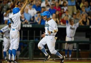 Photo - UCLA's Brian Carroll (24), left, and Eric Filia (4) celebrate after scoring off a double hit by Pat Valaika (10) against North Carolina in the bottom of the seventh inning in Game 12 of the College World Series at TD Ameritrade Park in Omaha, Neb., Friday, June 21, 2013. (AP Photo/The Omaha World-Herald/Matt Miller) MAGAZINES OUT; ALL LOCAL TV OUT