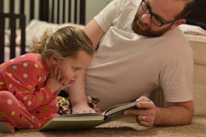 Photo - Isabella and Michael Mitchell, of Edmond, look at a book together.  Photo provided <strong></strong>