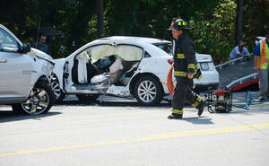 Photo - FILE - This May 13, 2014 file shows a North Lenoir, N.C. firefighter taking equipment back to the truck after a woman, pinned in her white vehicle, was rescued by the jaws of life, in Kinston, N.C. The economic and societal harm from motor vehicle crashes amounted to a whopping $871 billion in a single year, according to a study released Thursday by the National Highway Traffic Safety Administration. The study examined the economic toll of car and truck crashes in 2010, when 32,999 people were killed, 3.9 million injured and 24 million vehicles damaged. Those deaths and injuries were similar to other recent years.(AP Photo/Daily Free Press, Janet S. Carter)