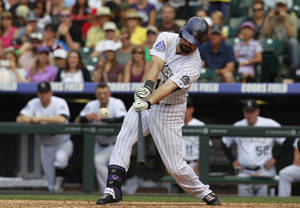 Photo - Colorado Rockies' Todd Helton connects on a double off Cincinnati Reds relief pitcher Curtis Partch in the seventh inning of a baseball game in Denver on Sunday, Sept. 1, 2013. The double was the 2,500th hit in Helton's career. (AP Photo/David Zalubowski)