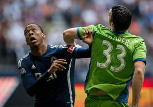 Photo - Vancouver Whitecaps' Carlyle Mitchell, left, vies for position with Seattle Sounders' Kenny Cooper during the first half of an MLS soccer game in Vancouver, British Columbia, on Saturday, July 5, 2014. (AP Photo/The Canadian Press, Darryl Dyck)