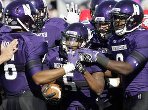 Photo -   Northwestern running back Venric Mark (5) celebrates a touchdown with teammates during the first half of an NCAA college football game against South Dakota in Evanston, Ill., Saturday, Sept. 22, 2012. (AP Photo/Nam Y. Huh)
