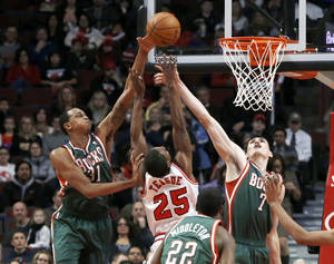Photo - Milwaukee Bucks forward John Henson, left, blocks the shot of Chicago Bulls point guard Marquis Teague (25) as Ersan Ilyasova (7) also defends during the first half of an NBA basketball game Tuesday, Dec. 10, 2013, in Chicago. (AP Photo/Charles Rex Arbogast)