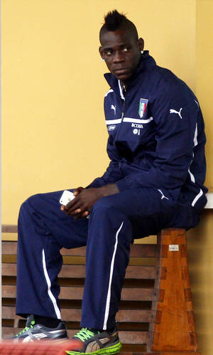 Photo - Italy's Mario Balotelli waits for the start of a training session at the Coverciano training grounds, near Florence, Italy, Monday, Oct. 7, 2013. Italy is scheduled to play a Would Cup qualifier soccer match against Denmark, in Copenhagen Friday Oct. 11. (AP Photo/Fabrizio Giovannozzi)