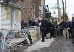 Photo - <p>President Barack Obama visits with people on Cedar Grove Avenue, a street significantly impacted by Superstorm Sandy, on the Staten Island borough of New York, Thursday, Nov. 15, 2012. (AP Photo/Carolyn Kaster)</p>