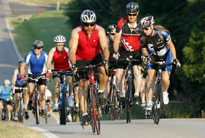 Photo - Riders head east on Robinson Street during the annual Norman Conquest bike ride that benefits the J.D. McCarty Center. PHOTO BY STEVE SISNEY, THE OKLAHOMAN <strong>STEVE SISNEY</strong>