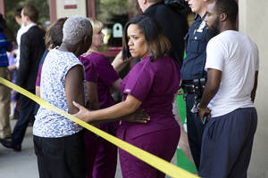 Photo - A hospital worker views police activity near the scene of a shooting at a wellness center attached to Mercy Fitzgerald Hospital in Darby, Pa., on Thursday, July 24, 2014. A doctor grazed by gunfire from a patient who had entered his office in a suburban hospital's psychiatric unit stopped him by returning fire with his own gun and injuring him, authorities said. (AP Photo)