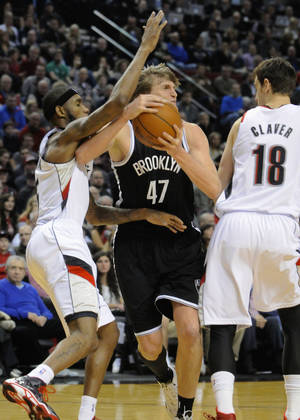 Photo - Brooklyn Nets' Andrei Kirilenko (47) drives against Portland Trail Blazers' Will Barton (5) and Victor Claver (18) during the first half of an NBA basketball game in Portland, Ore., Wednesday, Feb. 26, 2014. AP Photo/Greg Wahl-Stephens)