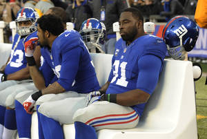 Photo - New York Giants defensive end Justin Tuck, right, sits on the bench in the final minutes of an NFL football game against the Seattle Seahawks, Sunday, Dec. 15, 2013, in East Rutherford, N.J. (AP Photo/Bill Kostroun)