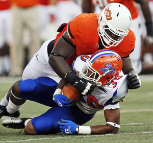 Photo - OSU's Calvin Barnett (99) brings down Lereginald Veals (30) of Savannah State during a college football game between Oklahoma State University (OSU) and Savannah State University at Boone Pickens Stadium in Stillwater, Okla., Saturday, Sept. 1, 2012. Photo by Nate Billings, The Oklahoman