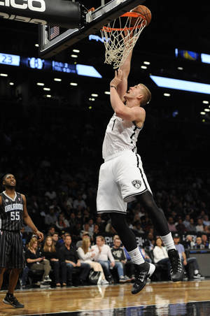 Photo - Brooklyn Nets' Mason Plumlee (1) releases a shot as Orlando Magic's E'Twaun Moore (55) watches during the first half of an NBA basketball game Sunday, April 13, 2014, in New York. The Nets won 97-88. (AP Photo/Kathy Kmonicek)