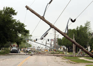 photo - Power poles block 24th Ave. SW following Friday's tornado on Saturday, April 14, 2012, in Norman, Okla.  Photo by Steve Sisney, The Oklahoman