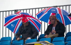 photo -   Race watchers take shelter during practice at the Silverstone circuit, England, Friday, July 6, 2012. The Formula 1 teams make preparations ahead of the British Grand Prix at Silverstone circuit on Sunday. (AP Photo/Tom Hevezi)