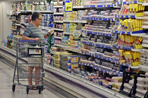 Photo -   A shopper looks at an item in the dairy section of a Kroger grocery store in Richardson, Texas.  AP Photo  <strong>LM Otero -  AP </strong>