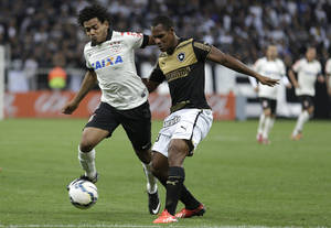 Photo - Corinthians's Romarinho, left, fights for a ball with Botafogo's Andre Bahia during a Brazilian soccer league match at the Itaquerao, the stadium that will host the World Cup opener match between Brazil and Croatia on June 12, in Sao Paulo, Brazil, Sunday, June 1, 2014. (AP Photo/Andre Penner)