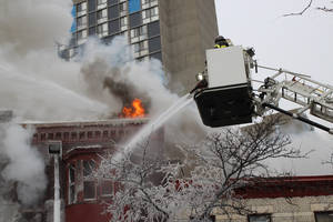 Photo - Crews battle a Minneapolis apartment fire on Wednesday, Jan. 1, 2014. The billowing fire engulfed a three-story building, sending 13 people to hospitals with injuries ranging from burns to trauma associated with falls. (AP Photo/Jeff Baenen)