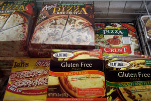 Photo - FILE - This Nov. 11, 2008, file photo, shows gluten-free frozen pizza, just one of hundreds of items at Gluten Free Trading Co. in Milwaukee. Schools, restaurants and anyone else serving food are more vulnerable to legal threats over food sensitivities after the Justice Department determined that severe food allergies can be classified as disabilities under federal law. People who suffer from celiac disease don't absorb nutrients well and can get sick from the gluten found in wheat, rye and barley. Celiac is a diagnosed illness that is more severe than gluten sensitivity, which some people self-diagnose. Millions of people are buying gluten free foods because they say they make them feel better, even if they don't have a wheat allergy. (AP Photo/M.L. Johnson, File)