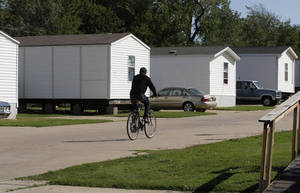 photo -   A resident rides a bicycle on the grounds of Hand Up Ministries in Oklahoma City, Wednesday, Oct. 3, 2012. Hand Up Ministries is a non profit faith-based organization that offers help to men and women coming out of the prison system to re-enter society. The grounds currently house 150 sex offenders and 7 other felons. (AP Photo/Sue Ogrocki)