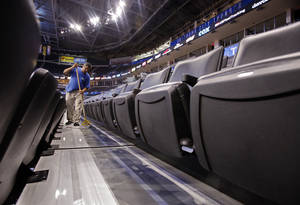 photo - Gerardo Basquiec mops between seats in preparation for the first game of the NBA basketball finals at the Chesapeake Arena on Tuesday, June 12, 2012 in Oklahoma City, Okla. Photo by Steve Sisney, The Oklahoman <strong>STEVE SISNEY</strong>