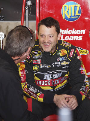 Photo - Driver Tony Stewart talks with a crew member in the garage after practice for Sunday's NASCAR Sprint Cup series auto race at Martinsville Speedway in Martinsville, Va., Saturday, April 6, 2013. (AP Photo/Steve Sheppard)