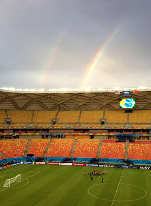 Photo - A rainbow is seen as members of the United States men's soccer team train at Arena da Amazonia in Manaus, Brazil, Sunday, June 22, 2014. The U.S. will play against Portugal on June 22 at the stadium during the 2014 soccer World Cup. (AP Photo/Ronald Blum)